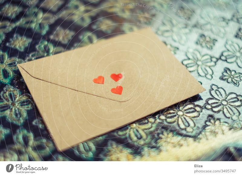 Ein mit drei roten Herzen dekorierter Briefumschlag, der auf einem ornamentalem Hintergrund liegt; Liebesbrief Muttertag Geschenk Kommunikation Nachricht