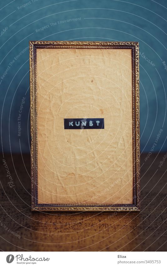Ein goldener mit Ornamenten verzierter Bilderrahmen in dem das Wort Kunst geschrieben steht Symbol Buchstaben kritisch Rahmen alt zerknittert antik