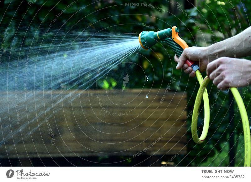 Zwei kräftige Hände vor braunem und dunkelgrünem Hintergrund halten einen gelben Gartenschlauch mit einem grün organge farbenen Duschkopf aus dem ein heller Brausestrahl frischen Wassers kommt, während einige kleine Tropfen senkrecht herabfallen