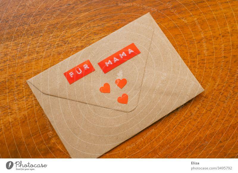 Ein Briefumschlag auf dem Für Mama steht mit drei roten Herzen dekoriert auf einem Untergrund aus Holz; Nachricht Geschenk an die Mutter zu Muttertag Liebe