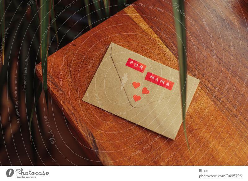 Ein Briefumschlag auf dem Für Mama steht mit drei roten Herzen dekoriert auf einem Untergrund aus Holz; Brief Geschenk an die Mutter zu Muttertag Liebe