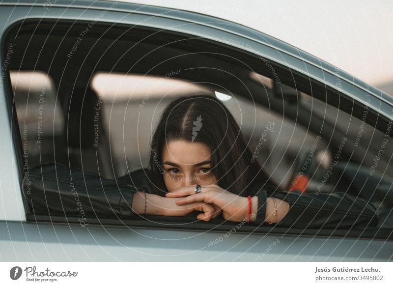 junges Mädchen, das sich an die Scheibe eines grauen Autos lehnt Mensch Fahrer Reisefotografie PKW Porträt Vintage-Mädchen Leben coche schön niedlich Model