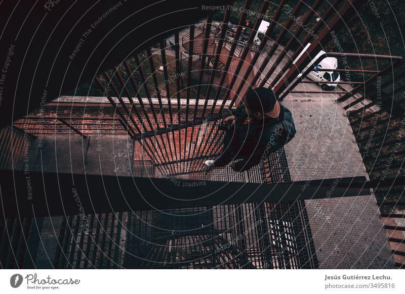 Mann mit Mütze geht eine Metalltreppe hinunter Hafengebiet Wasser Ansicht Victoria Peak Dämmerung urban Hafen von Victoria reisen Reiseziel Tourismus
