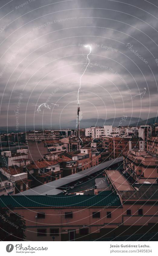 Blitzschlag in eine Antenne mit einer Stadt im Hintergrund, mitten in einem Sturm Hafengebiet Wasser Ansicht Victoria Peak Dämmerung urban Hafen von Victoria