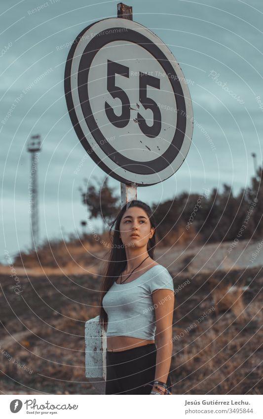 junges Modell, das ein weißes Oberteil mit einem Poster dahinter trägt Stil Frau Farbfoto schön Junge Frau Farbe Mensch Porträt Phantasie Mysterium Licht