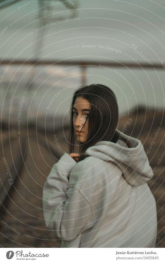 junge Frau mit Kapuze in einem weißen Sweatshirt mit ernstem Blick altehrwürdig Hintergrund Behaarung Gesicht Mädchen Menschen Außenaufnahme Beautyfotografie