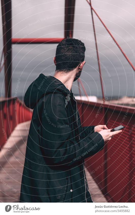 Mann in schwarzem Mantel, der ein Mobiltelefon auf einer roten Brücke hält Tag Stadt Brückenbau Ferien & Urlaub & Reisen Architektur Brückenpfeiler Himmel