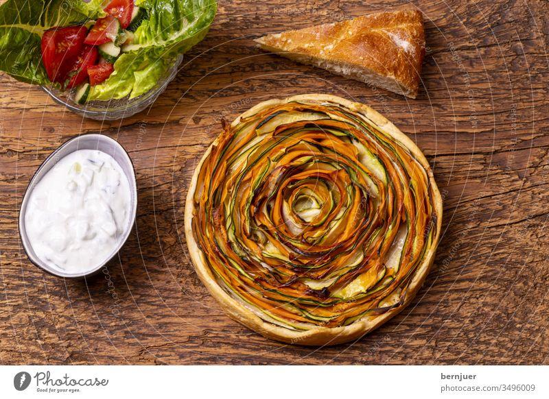 Kuchen mit Karotten und Zucchini auf Holz Zucchinikuchen Muster Aufsicht Planke rustikal rund herzhaft Gourmet zubereitet gekocht gesund Gebäck Gartengemüse
