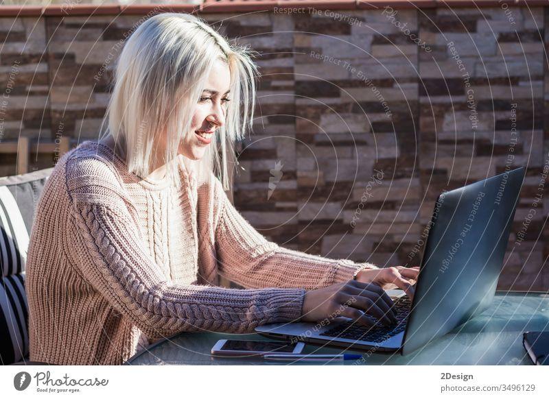 Studentin, die einen Laptop benutzt, während sie draußen auf der heimischen Terrasse sitzt. Frau jung heimwärts Mädchen Computer Glück Menschen Person Lifestyle