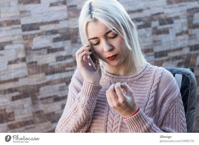 Junge, hübsche Frau, die auf dem Sofa auf der Terrasse sitzt und telefoniert 1 Mobile Handy sprechend Telefon heimwärts im Freien Freizeitkleidung Erwachsener