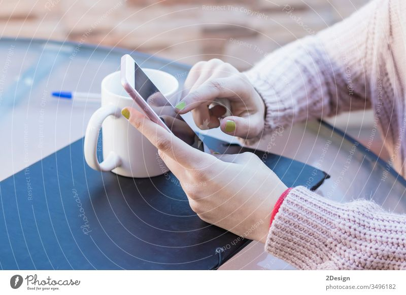 Makroaufnahme der Hände eines Mädchens, das Nachrichten auf einem Smartphone liest. Sie berührt den Touchscreen mit ihrem Finger, um die Seite umzublättern. 1