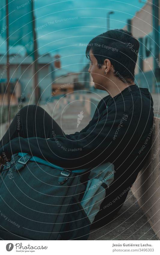 Junger Rucksacktourist sitzt auf einer Tribüne mit blauem Hintergrund Farbfoto Außenaufnahme Porträt klassisch Person Mann Wanderer Leben schön Model Straße