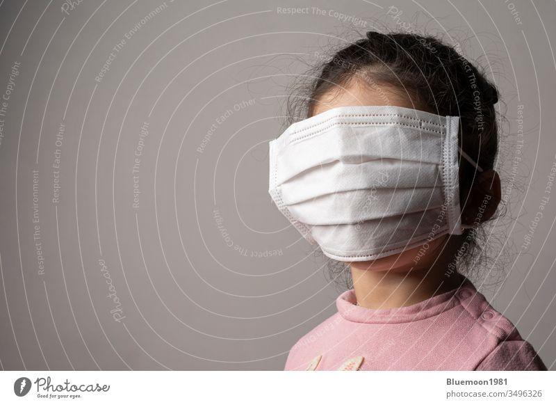 Gedecktes Gesicht eines kleinen Mädchens mit Schutzmaske eines Krankenhauses tragend Mundschutz Kind Konzept Virus Korona medizinisch Pandemie Porträt Kinder