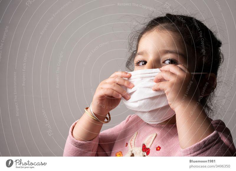 Porträt eines kleinen Mädchens mit Maske zum Schutz vor dem epidemischen Coronavirus tragend Krankenhaus Mundschutz Kind Konzept Virus Korona medizinisch