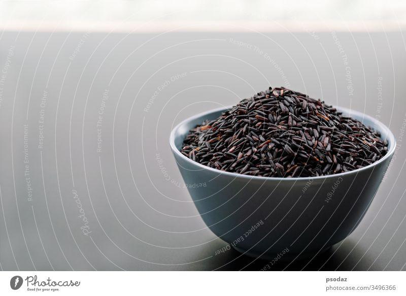 Schale mit schwarzem Jasminreis auf schwarzem Hintergrund landwirtschaftlich Ackerbau Agrarwissenschaftler Asien asiatisch Hintergründe Beeren