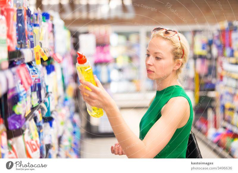 Frau kauft Reinigungskräfte im Supermarkt ein. Laden Kunde Markt Verbraucher Korb Menschen jung Spülmittel Seife Waschmittel Werkstatt Person kaufen Gewerbe