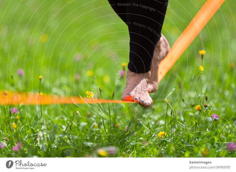 Slackline im Stadtpark. Schlaffleitung Aktivität Sport schlaff Linie Frau Gleichgewicht Drahtseil jung Person Seil Fitness Rücken Natur Konzentration passen