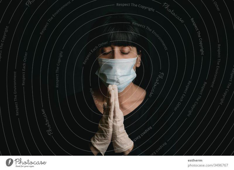 junge Frau, die eine medizinische Maske für Coronavirus trägt, mit zusammengeklappten Händen betend covid-19 Junge Frau 2019-ncov Virus Seuche Pandemie