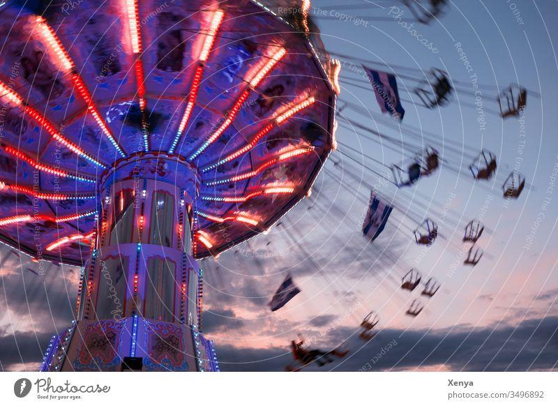 Karusell bei Nacht Bewegung Freude Jahrmarkt Fahrgeschäfte fliegen drehen blau rote Lichter Wellenflug Kettenkarusell Schwungvoll Oktoberfest Freizeit & Hobby