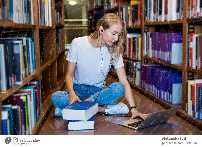 Junges Mädchen, das in der traditionellen Bibliothek am Boden in Bücherregalen sitzt und Bücher liest. Lächelnde und lachende Studentin, die mit dem Laptop arbeitet, lernt. Hochschulbildung.  Studentisches Leben