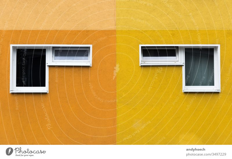 Ein Paar von zwei Fenstern an einer gelb-orangenen Fassade abstrakt Appartement Architektur Hintergrund Berlin Gebäude Gebäudeaußenseite gebaute Struktur