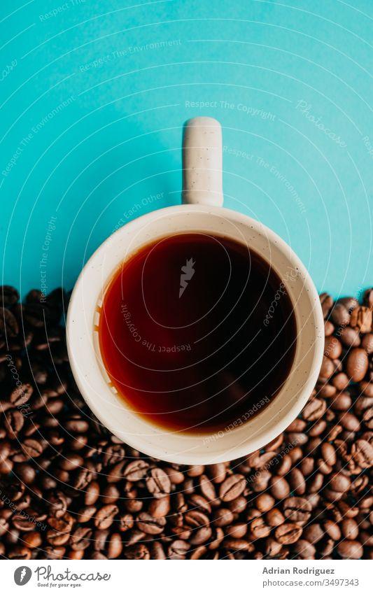 Nahaufnahme von oben einer Tasse Kaffee mit Kaffeebohnen auf blauem Hintergrund trinken Café jung Lifestyle Getränk Tisch heiß Aroma warm lässig Becher