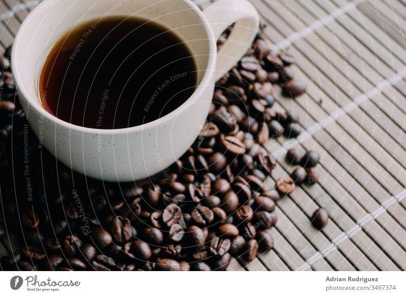 Nahaufnahme einer Tasse Kaffee mit Kaffeebohnen trinken Café jung Lifestyle Getränk Frau Tisch heiß Aroma warm weiß Erwachsener lässig Tee Becher Morgen