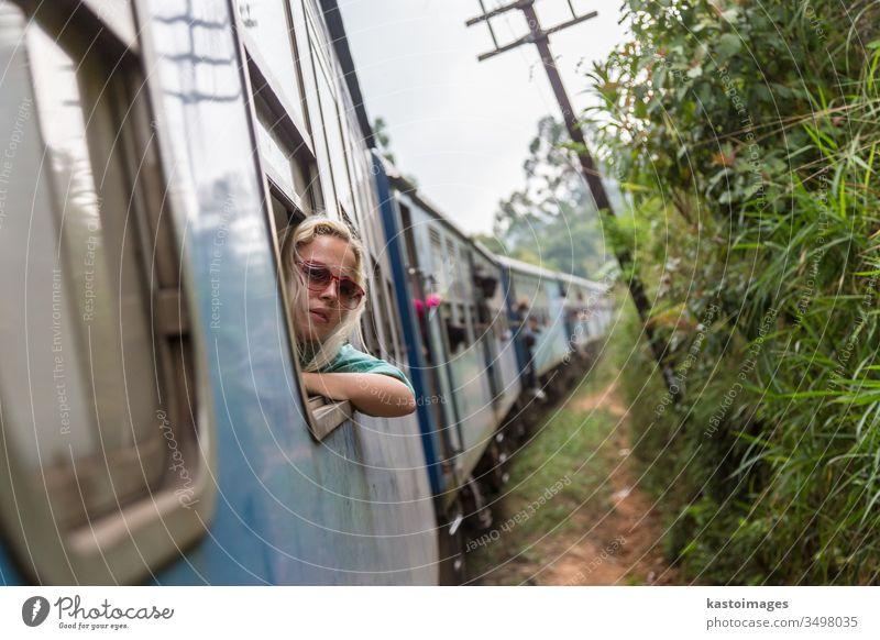 Blonde kaukasische Frau fährt im Zug und schaut durchs Fenster. reisen Verkehr Eisenbahn Blick Transport Abenteuer Passagier Reise im Innenbereich entspannend