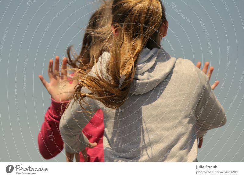 Kinder tanzen und springen Mädchen teenager lange Haare Pferdeschwanz Dynamisch Hände hoch fliegen Kapuzenjacke rosa grau Außenaufnahme abklatsch spielerisch