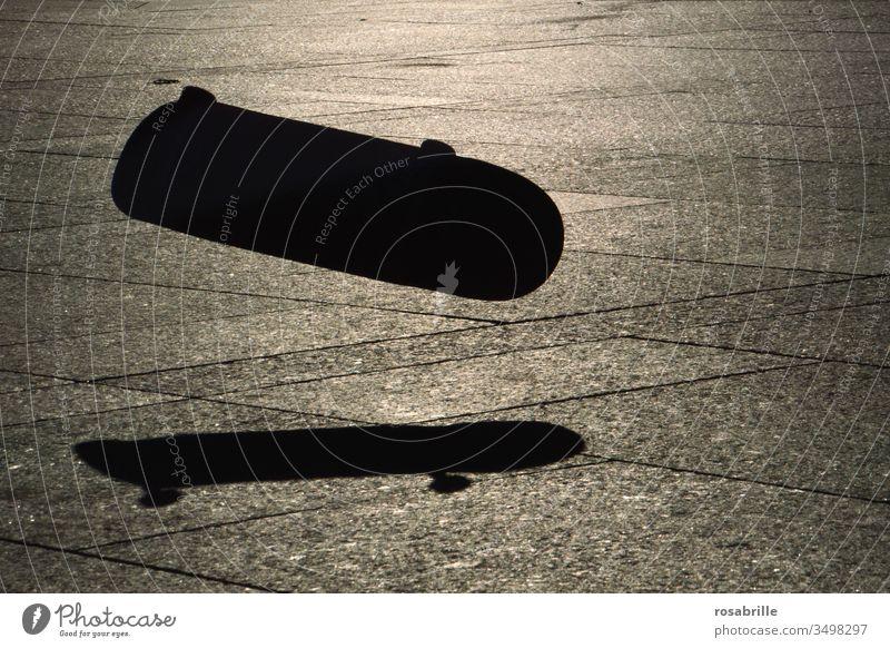 er sprang | knapp daneben | und sein Skateboard flog ohne ihn weiter Schatten springen Skateboardsprung Sonnenlicht Abendlicht Licht Silhouette menschenleer