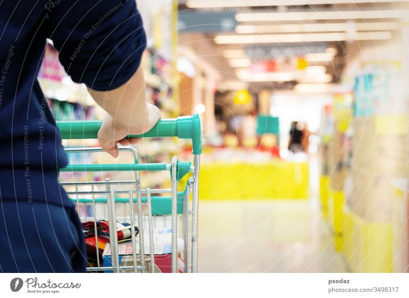 Einkäuferin mit Einkaufswagen mit verschwommener Bewegung eines Supermarkt-Kaufhauses Gang attraktiv Hintergrund Korb Business kaufen Karre Großstadt Gewerbe