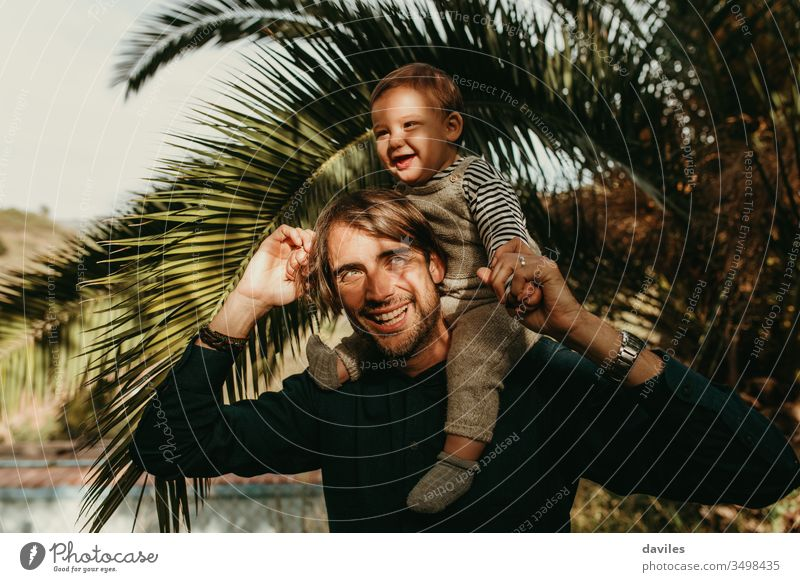 Lachender Vater, der seinen Sohn huckepack im Freien mit Sonnenlicht im Gesicht reitet. lieblich Lächeln weiß Spielen tragen Schultern gutaussehend freudig