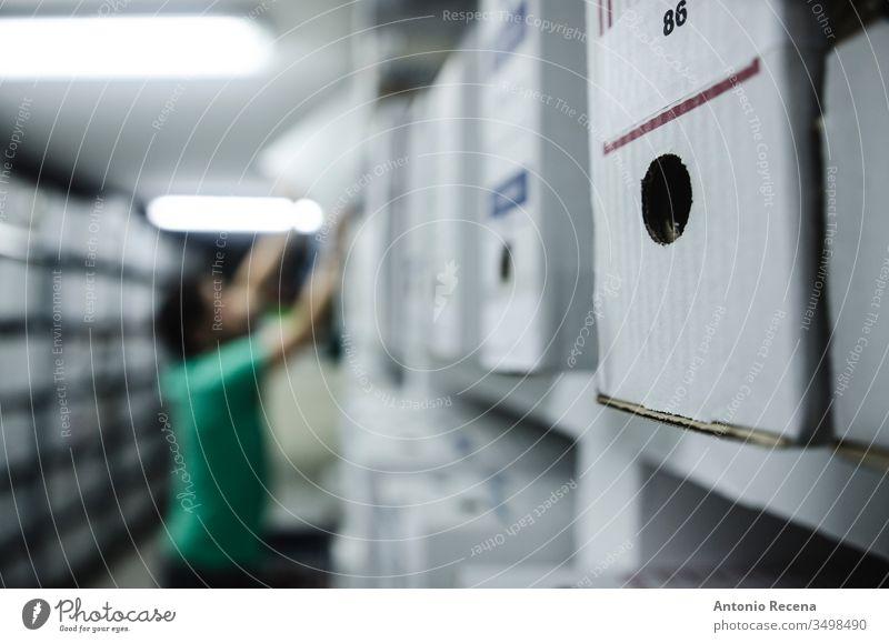 Dateiarbeiter verschwommen im Hintergrund, Fokus in der Dateibox Arbeit Arbeiter Dateien Keller im Innenbereich arbeiten Arbeitsplatz Kasten Papier Mann