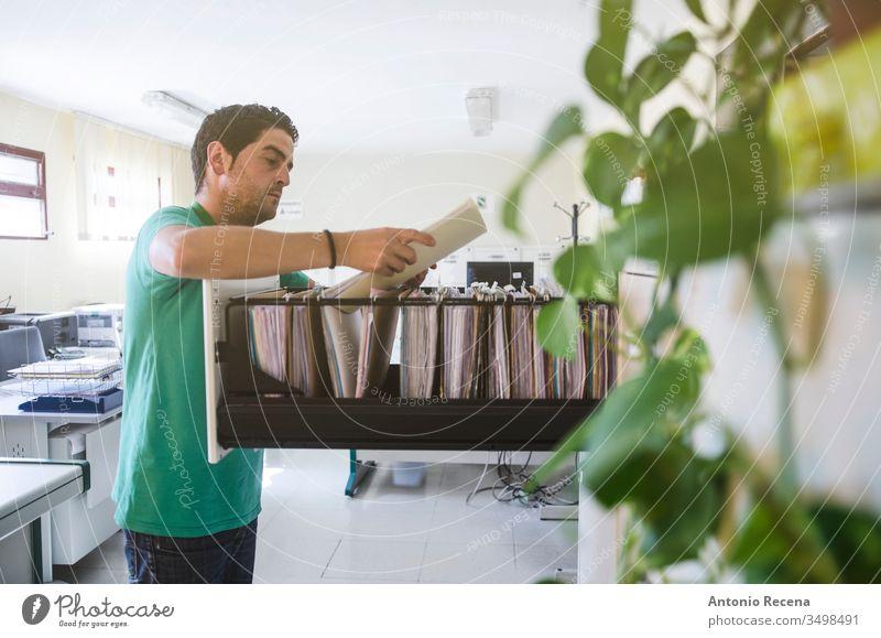 Büroangestellte im Büro, die in Schubladenordnern suchen Arbeiter Dateien Job Mann Dokumentation Arbeitsplatz Computer am Arbeitsplatz im Innenbereich