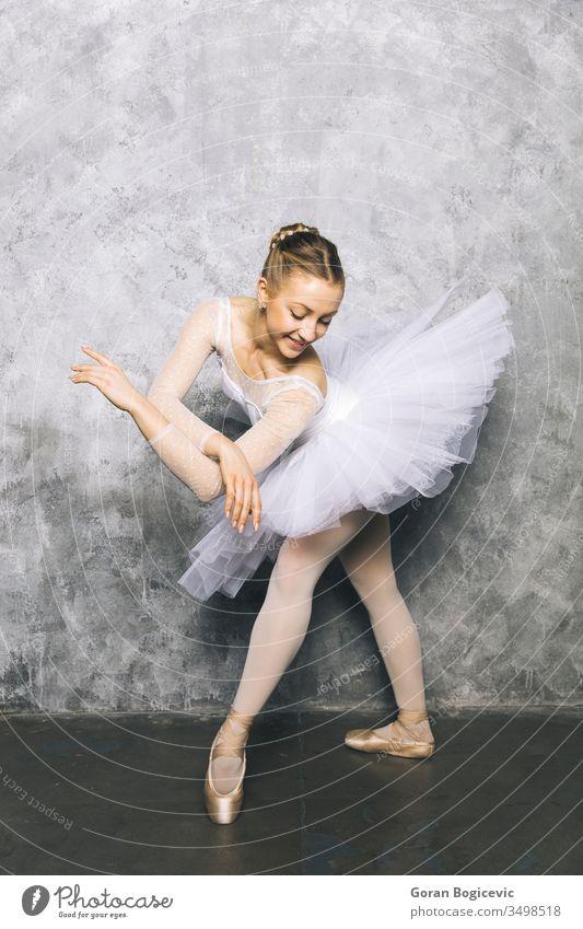 Hübsche junge Ballerina tanzt klassisches Ballett an rustikaler Wand Frau Tanzen Pose Tänzer Übung schön Schuhe Kleid Gleichgewicht Aktion Künstlerin