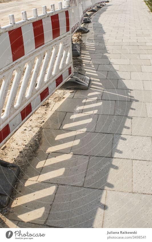 Schatten auf dem Gehweg von einem Bauzaun Absperrung Sicherheit Schutz Barriere Zaun Baustelle Strukturen & Formen Verbote Außenaufnahme Linie Menschenleer