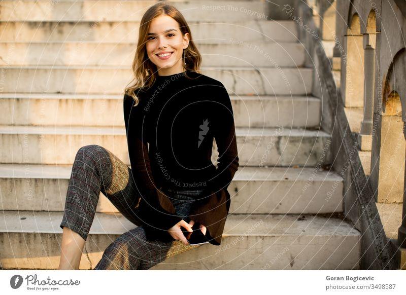 Junge Frau mit Mobiltelefon auf einer Treppe im Freien sitzend Telefon Mobile jung Schönheit Person Erwachsener Glück schön benutzend Porträt Sitzen