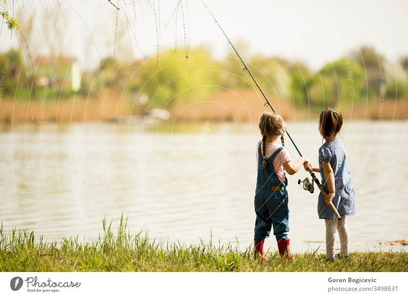 Zwei kleine Mädchen beim Angeln Aktivität fangen Kaukasier Kind Kindheit niedlich Genuss Frau Fisch Fischer Fischen Spaß Fröhlichkeit Glück Halt Freude See