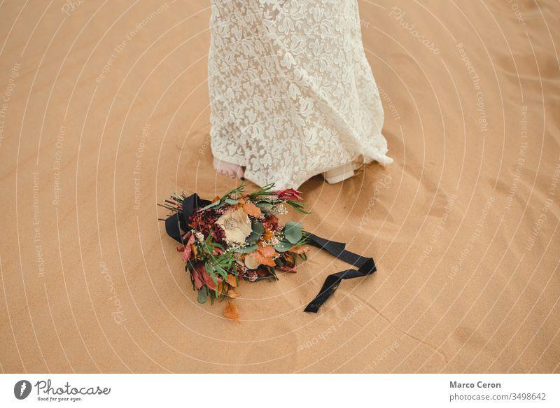 Brautstrauß, der neben den Füßen der Braut auf dem Sand liegt. Blume Frau Blumenstrauß außerhalb Kleid im Freien Dekoration & Verzierung Ordnung geblümt