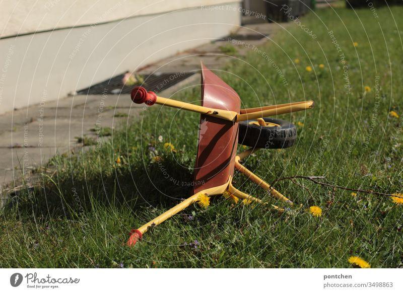 Kinderspielzeug Schubkarre steht hochkant auf einer Wiese. Gartenarbeit wiese löwenzahn grün natur hobby spielen gärtner Gärtner Gras Farbfoto Außenaufnahme