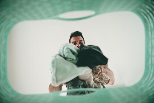 Mann mit Wäsche in der Hand schmeißt Schmutzwäsche in den Wäschekorb - Hausmann Haushalt Hausarbeit Waschen Froschperspektive zu Hause Ordnung aufräumen