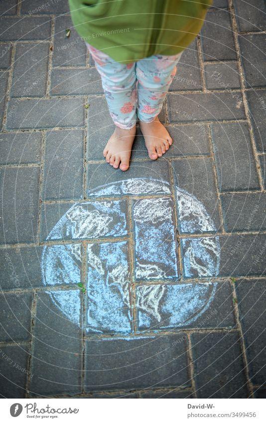 Wörtlich genommen l Die Welt liegt dir zu Füßen Kind Erde Kreide Zeichnung Leben Kindheit Tag Kunst Farbfoto Kreativität Außenaufnahme Nachhaltigkeit Umwelt