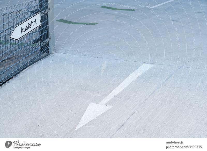 Eine Ausfahrt mit Pfeil in einem Parkhaus abstrakt Architektur Pfeilsymbol Asphalt Hintergrund Gebäude Zement Großstadt Mitteilung Konzept konzeptionell Beton