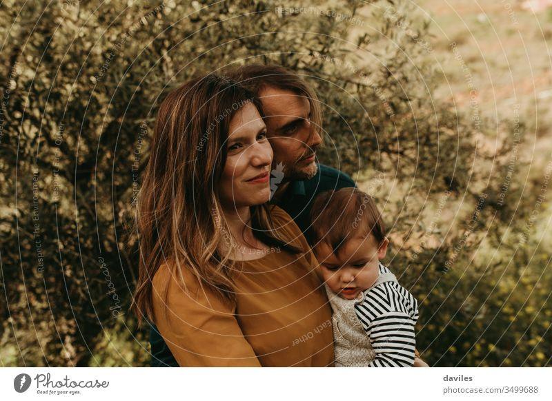 Ehepaar, das mit seinem Sohn im Freien steht. Konzept der jungen Familie. Die Mutter hält das Kind in den Armen. Mann und Frau schauen entspannt weg. Glück Park