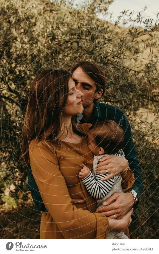 Ehepaar, das mit seinem Sohn im Freien steht. Konzept der jungen Familie. Die Mutter hält das Kind in den Armen. Mann küsst die Frau auf die Wange. Glück Park