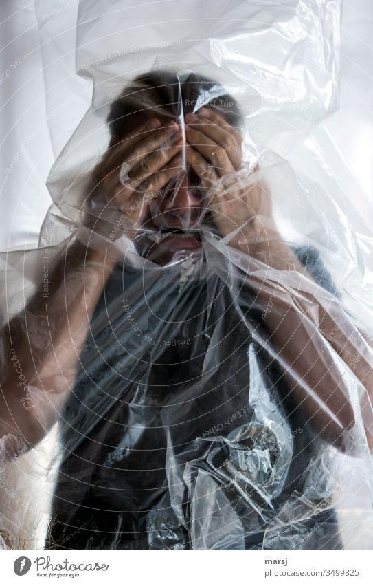 gefangen in plastik | Ein Mann, der vor lauter Panik die Hände vor das Gesicht hält Schutzhaltung Feindseligkeit Frustration abwehrend verdecken schützend