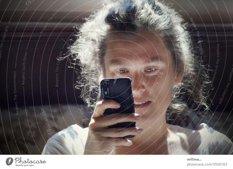 Smartphoneliebe Frau junge Frau SMS Nachricht lesen Whatsapp Handy freuen lächeln Freude Gegenlicht kommunizieren E-Mail Internet