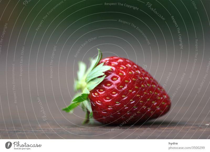 reife rote Erdbeere mit grünen Blättern liegt auf braunem Tisch Erdbeeren Frühling Frucht saftig süß rein lecker Gesundheit Gesunde Ernährung Bioprodukte