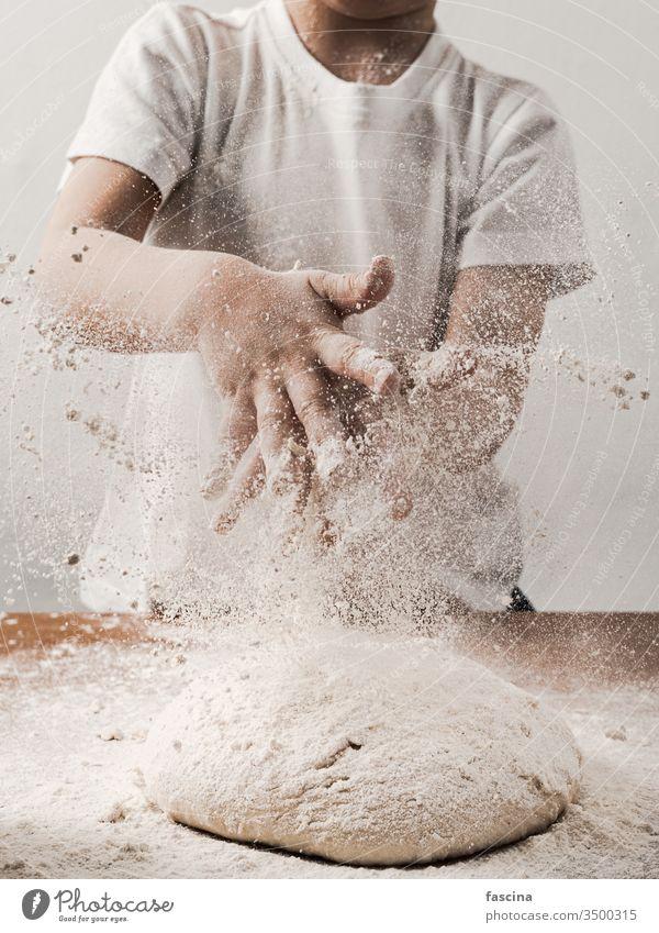 Zicklein, das mit Mehl über den Teig klatscht, senkrecht Ernte unkenntlich Kind Person Klatschen Hände während Essen zubereiten Brot Berieselung weiß vorbei