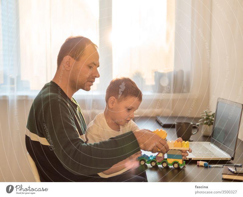 Konzept der Fernarbeit unter Kindern aus der Ferne arbeiten vier Jahr alt Junge spielen Laptop Gebäude Kulisse Papa die Werk heimwärts Coronavirus Quarantäne